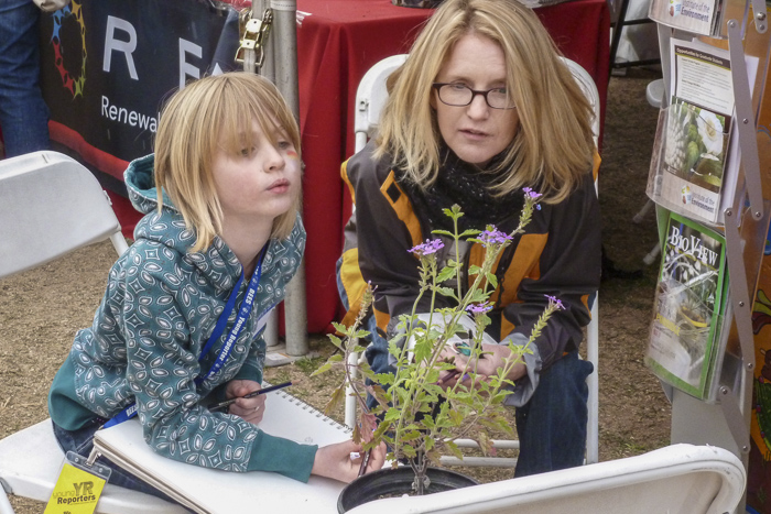 Meredith coaches a young visitor in drawing a Verbena plant.